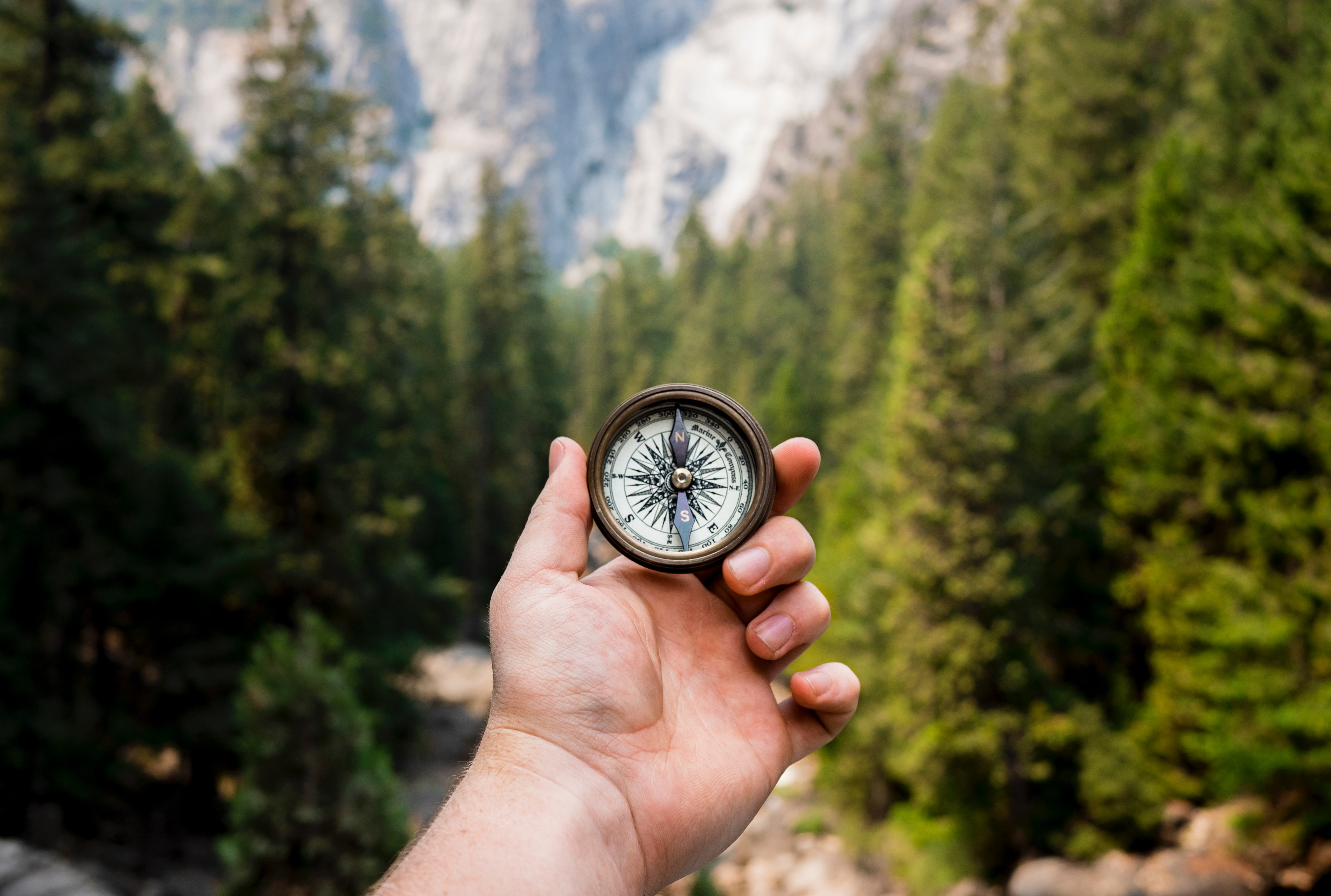 man holding compass overlooking valley