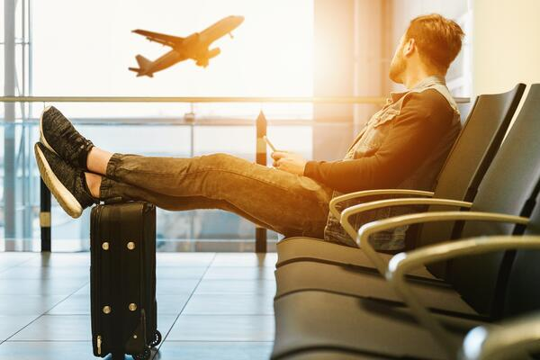 man waiting at airport with luggage